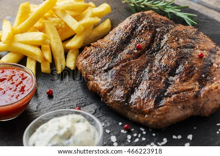Beef steak with french fries and sauce