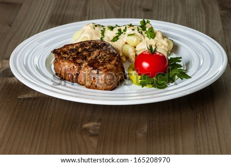Beef steak with gnocchi and gorgonzola sauce on plate - stock photo