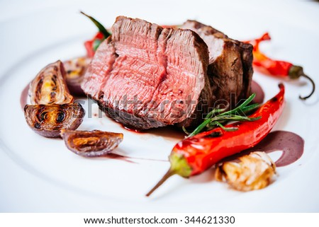 Beef steak with grilled vegetables served on white plate - stock photo