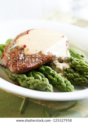 Beef steak with mustard sauce on green asparagus