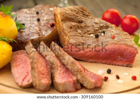 Beef steak with red and black pepper on wooden board - stock photo
