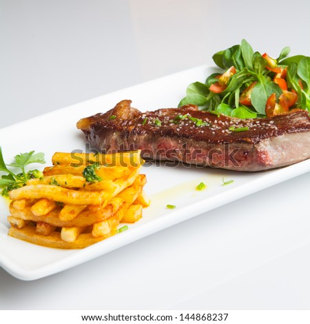 Beef Steak with salad and Fried chips.