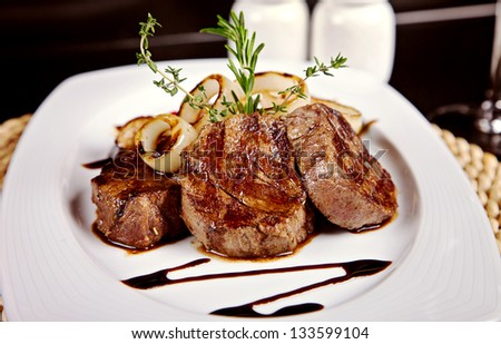 Beef steak with soy sauce, thyme, rosemary served on white plate in restaurant - stock photo