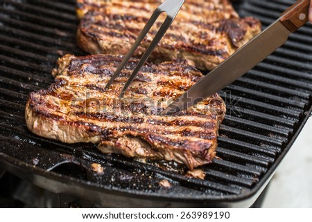 Beef steaks being prepared on grill with BBQ fork and knife with pepper, spices and seasoning with spatula - stock photo