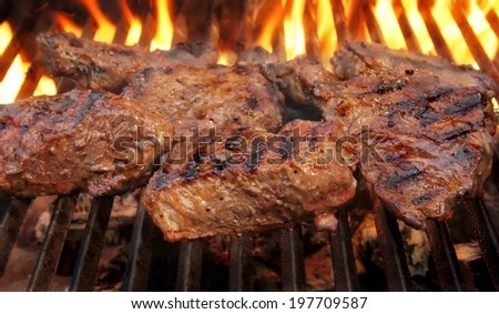 Beef steaks on the flaming grill.