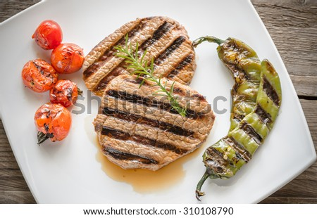 Beef steaks on the white square plate