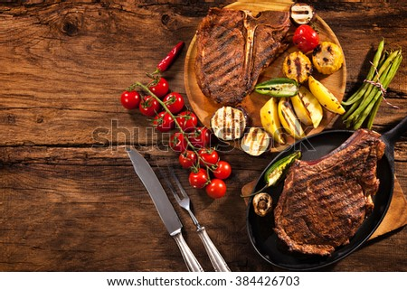 Beef steaks with grilled vegetables and seasoning on wood