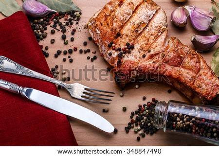 Beef steaks with spices on a wooden tray. Barbecue food