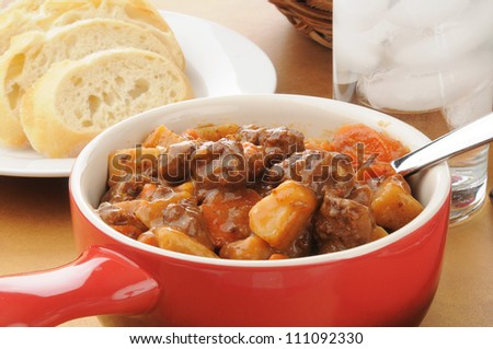 Beef stew in a red crock with bread
