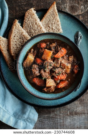 Beef Stew in turquoise bowl with bread - stock photo