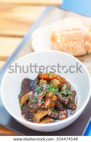 Beef stew or goulash in ceramic bowl and bread. - stock photo