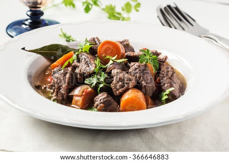 Beef stew with carrot on white napkin. Selective focus.