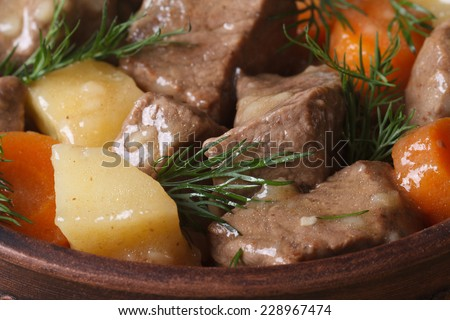 beef stew with vegetables and dill in a pot macro. horizontal top view. background  - stock photo