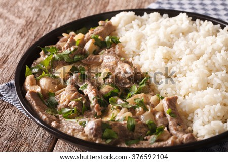 beef stroganoff garnished with rice close-up on a plate on the table. horizontal