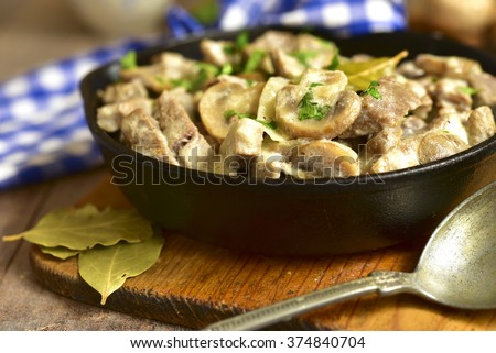 Beef stroganoff with mushrooms in a skillet pan on rustic background. - stock photo