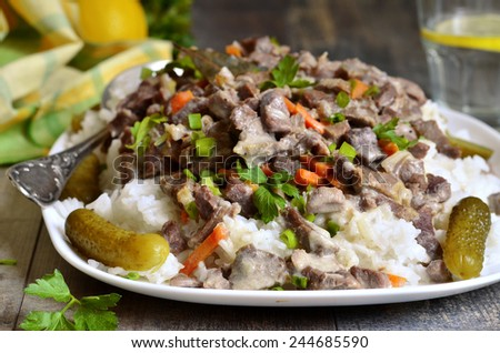 Beef Stroganoff with rice garnish and pickled cucumber. - stock photo