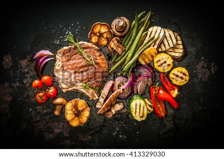 Beef T-Bone steak with grilled vegetables and seasoning on dark background - stock photo