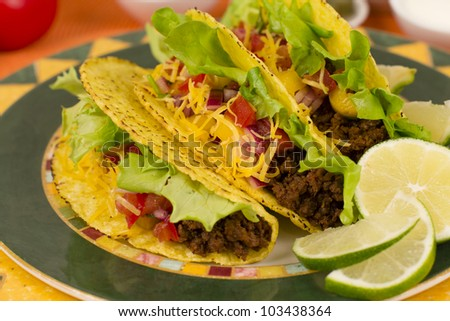 Beef Tacos - Mexican minced beef hard-shell tacos with salsa, cheese and lime wedges on a colourful plate. - stock photo