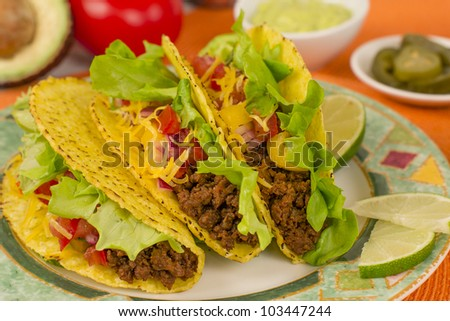 Beef Tacos - Mexican minced beef hard-shell tacos with salsa, cheese and lime wedges on a colourful plate. Guacamole and pickled jalapenos chilies on background. - stock photo