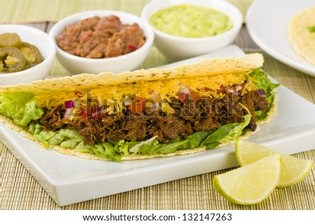 Beef Tacos - Mexican shredded beef tacos in soft corn tortillas served with lettuce, sour cream, grated cheddar cheese and salsa. Guacamole, refried beans and jalape�±os on the background.