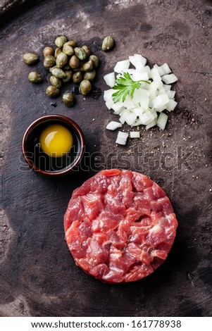 Beef tartar with capers and fresh onions on dark background - stock photo