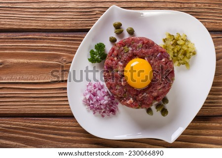beef tartare with egg, capers and cucumbers close-up on the table. horizontal top view  - stock photo