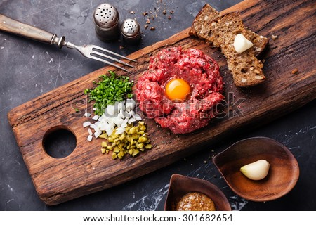 Beef tartare with pickled cucumber and fresh onions on dark marble background - stock photo