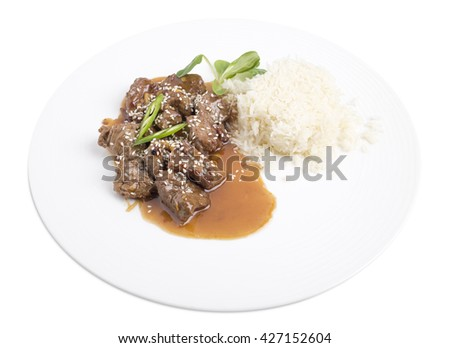Beef tenderloin with rice in oyster sauce with corn salad and sesame. Isolated on a white background. - stock photo