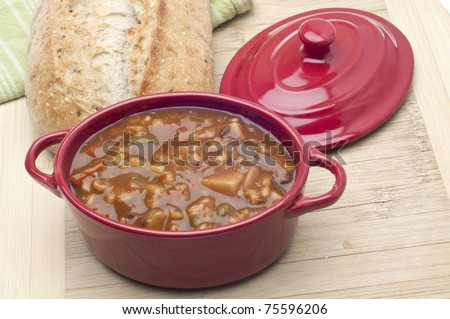 Beef Vegetable Soup in a Crock with Bread in the Background.