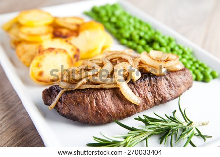 Beef with fried potatoes, onions and green peas - stock photo
