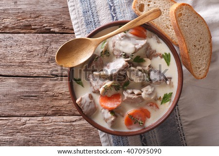Beef with mushrooms in cream sauce in a bowl on the table. horizontal view from above - stock photo