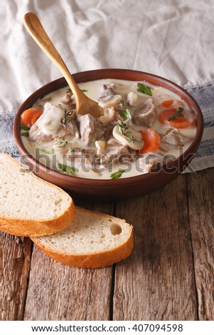 Beef with mushrooms in cream sauce in a bowl on the table. Vertical - stock photo