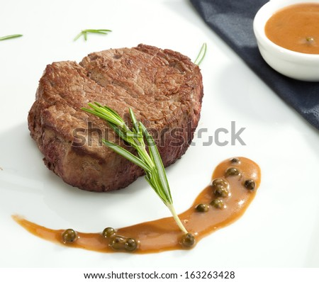 Beefsteak Tenderloin with the rosemary on the white plate - stock photo