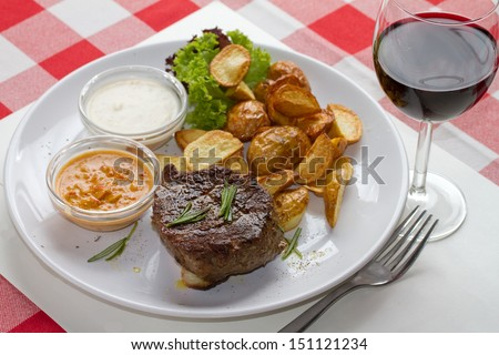 Beefsteak with home made potato fries two sauces, rosemary and glass of red wine - stock photo