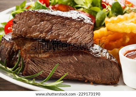 Beefsteaks, French fries and vegetables - stock photo