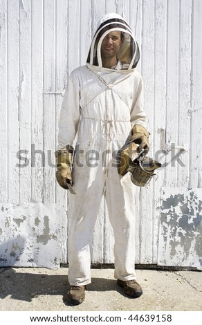 Beekeeper dressed in white hooded suit