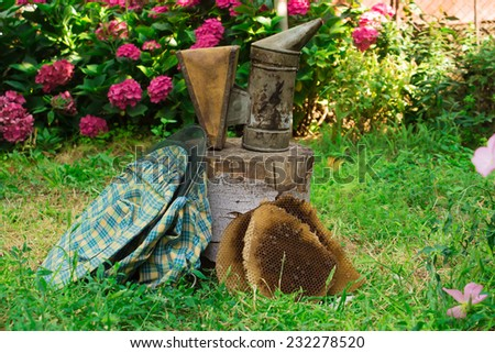 Beekeeping theme - smoker, protective hat, beeswax - stock photo
