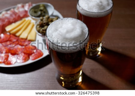 Beer and antipasto on a table - stock photo