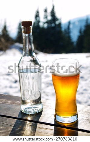 Beer and bottle of hard drink on wooden table in winter mountains - stock photo