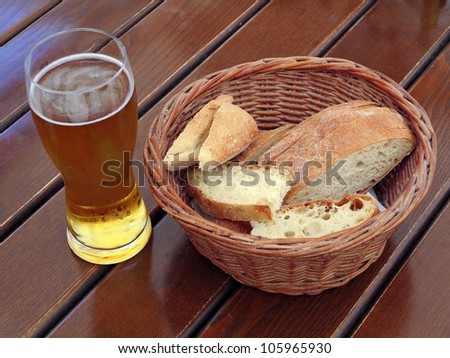 Beer and Bread on a wooden table - stock photo
