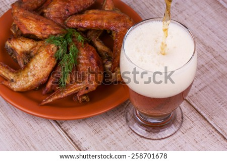 Beer and chicken wings on wooden background - stock photo