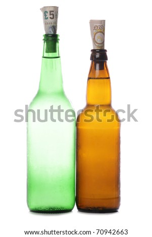 Beer and cider bottles with sterling money studio cutout - stock photo
