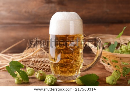 Beer and hops on wooden background