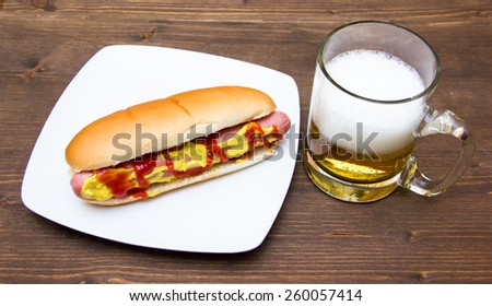 Beer and hot dogs on wooden table - stock photo