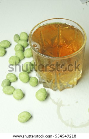 Beer and peanuts on the wooden background. Viewed from above.