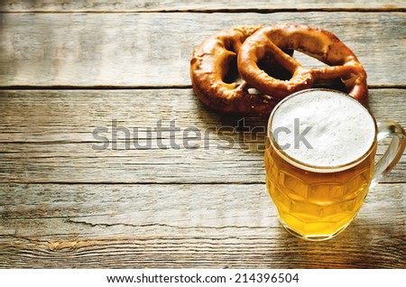 beer and pretzel on a dark wood background. tinting. selective focus on the foam in the glass - stock photo