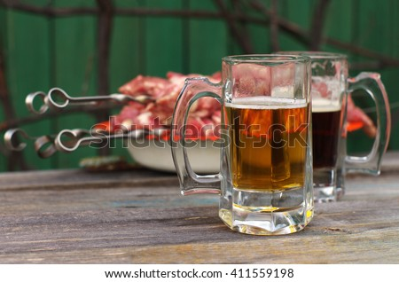 Beer and snack to beer. Fresh beer in a glasses and shish kebab on a skewer on a wooden simple surface. - stock photo