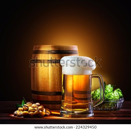 Beer barrel with beer glass on a wooden table. The dark background.  - stock photo