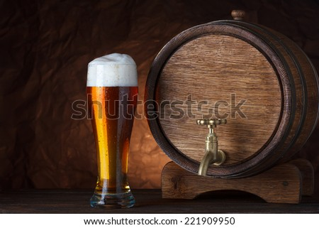 Beer barrel with beer glass on wooden table dark still-life - stock photo
