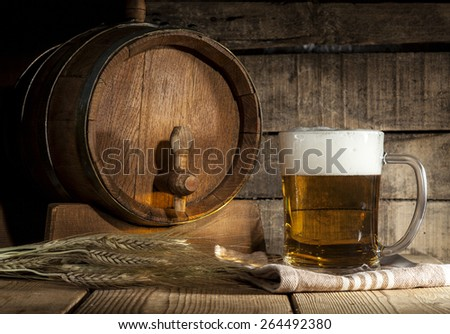 Beer barrel with beer mug on a wooden dark background.